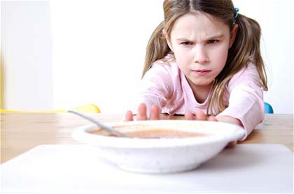 Close-up of a girl pushing a plate of soup on the table...A2NA8P Close-up of a girl pushing a plate of soup on the table